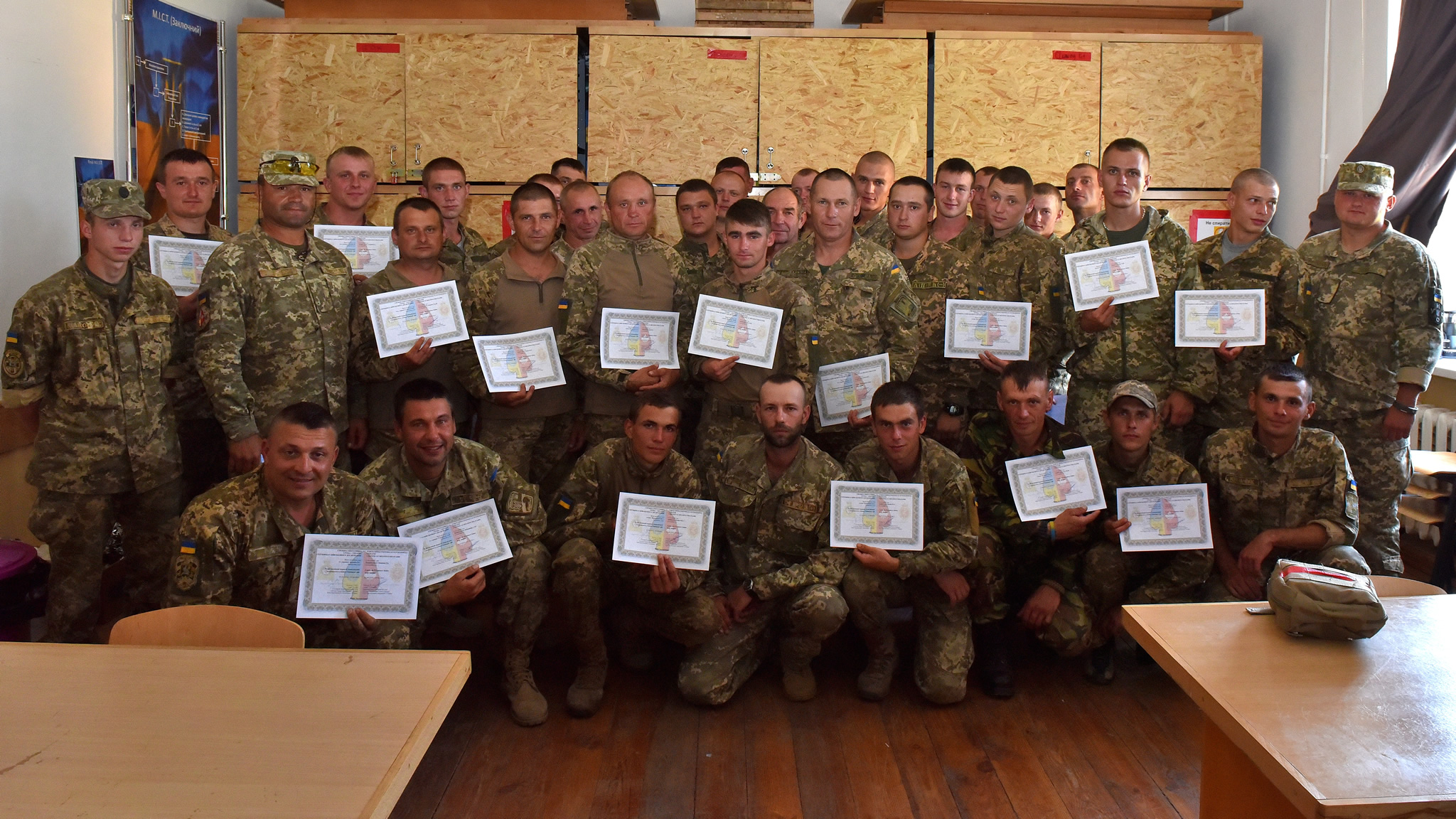 The Ukrainian instructors from the 184th Training Center and their students pose for a group picture holding their certificate confirming the completion of the Combat First Aid course in Yavoriv, on 3 August 2016 during Operation UNIFIER. The four instructors are part of the first group instructor qualified Ukrainians who are teaching the Canadian course to soldiers during the 55 day training block under the supervision of members of Joint Task Force Ukraine. (Photo : Capt J.P. Coulombe, JTF-U PAO)
