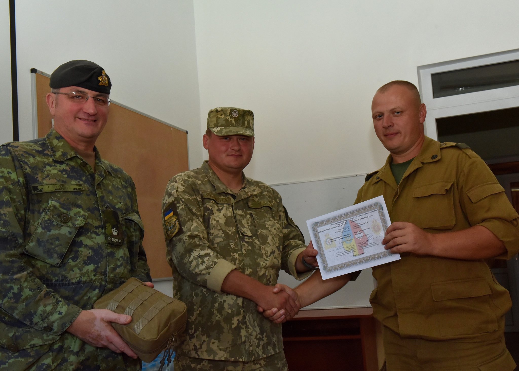 Maj Bruno Turmel, Deputy commander for Joint Task Force Ukraine, assists one of the four Ukrainian Instructors in presenting the course certificates for Combat First Aid to the students on 3 August 2016 during Operation UNIFIER. The four instructors are part of the first group instructor qualified Ukrainians who are teaching the Canadian course to soldiers during the 55 day training block under the supervision of members of Joint Task Force Ukraine. (Photo : Capt J.P. Coulombe, JTF-U PAO)