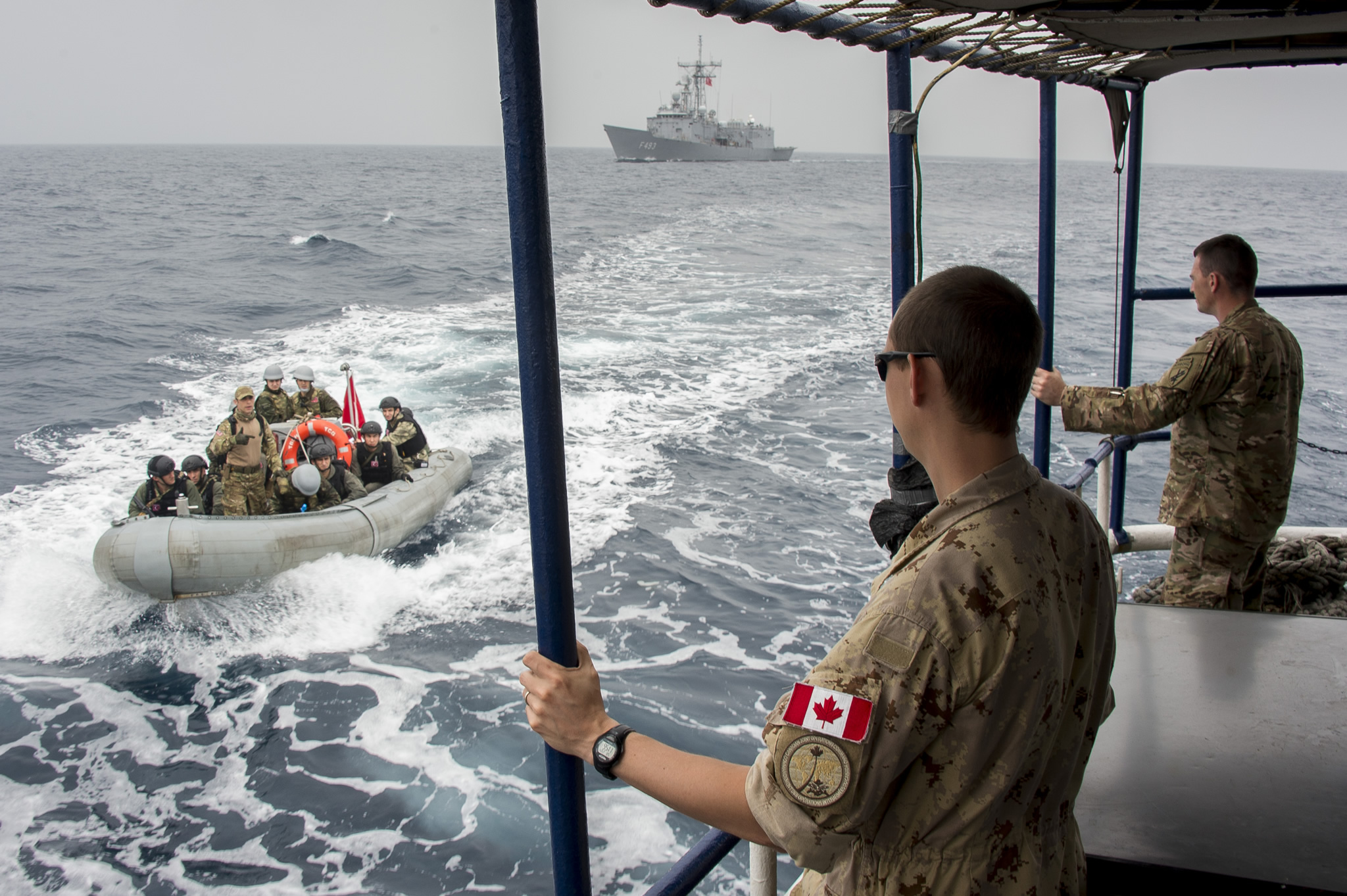 A Canadian military member watches a small speed boat come near the boat he's on