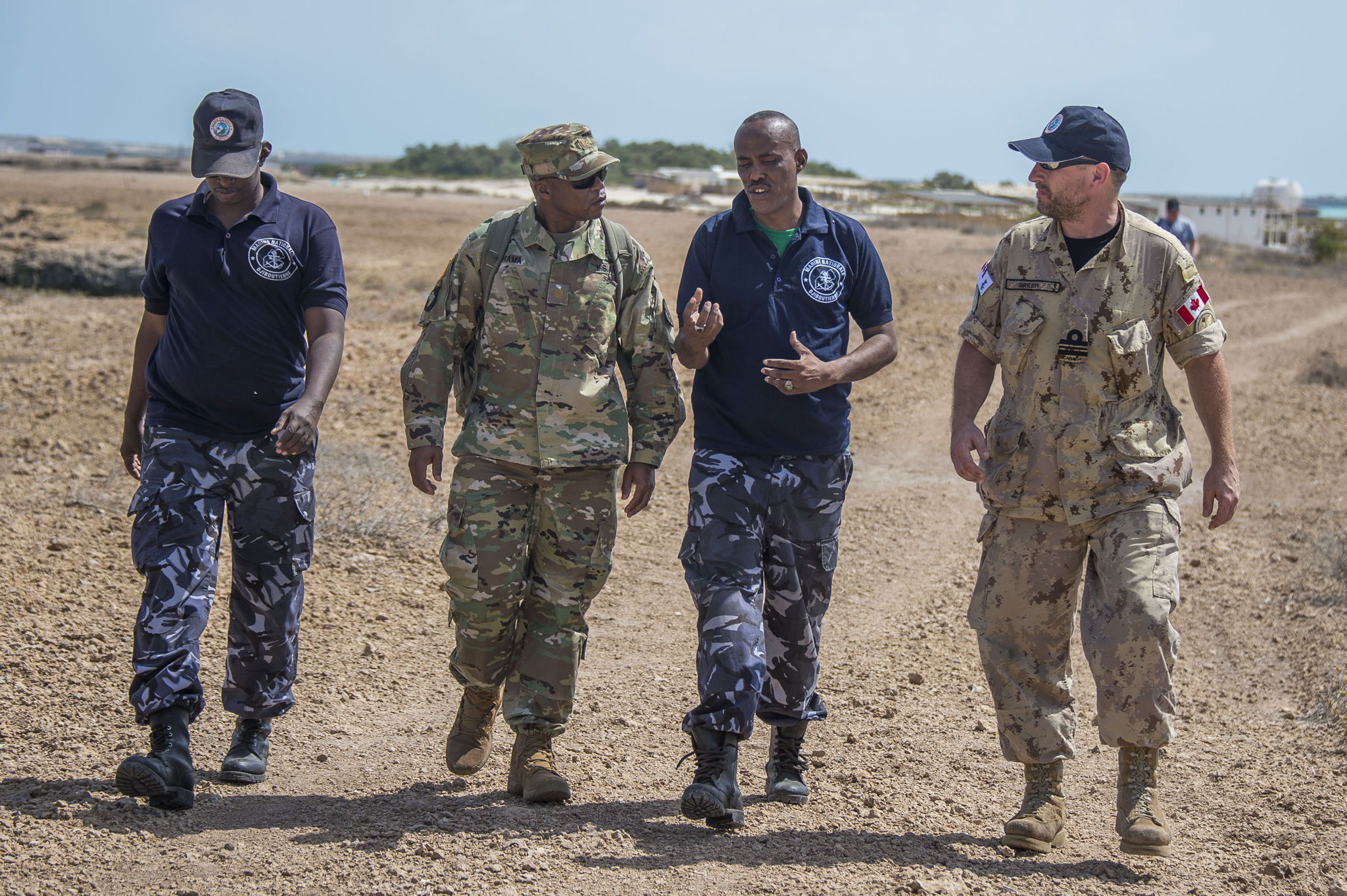 Four military members walk down a dirt road