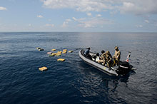 A Rigid Hulled Inflatable Boat from Her Majesty's Canadian Ship Edmonton with personnel from the United States Coast Guard recover bales of illicit drugs that were jettisoned into the Eastern Pacific Ocean during Operation CARIBBE on November 18, 2016. (Photo: MARPAC Imaging Services)