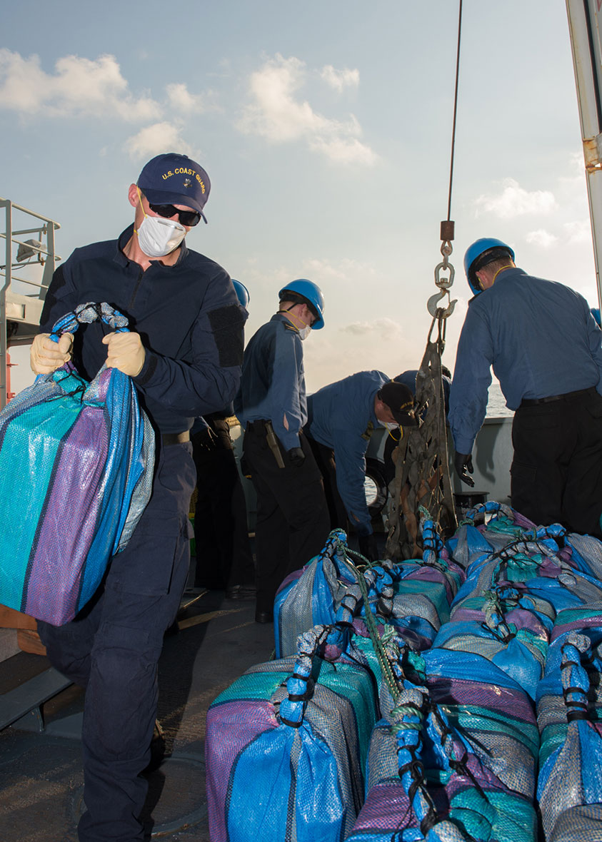 Operation CARIBBE. March 25, 2016. Canadian sailors and members from the United States Coast Guard Law Enforcement Detachment sort packages recovered after being tossed overboard from a vessel of interest. (Photo: OP Caribbe, DND.)