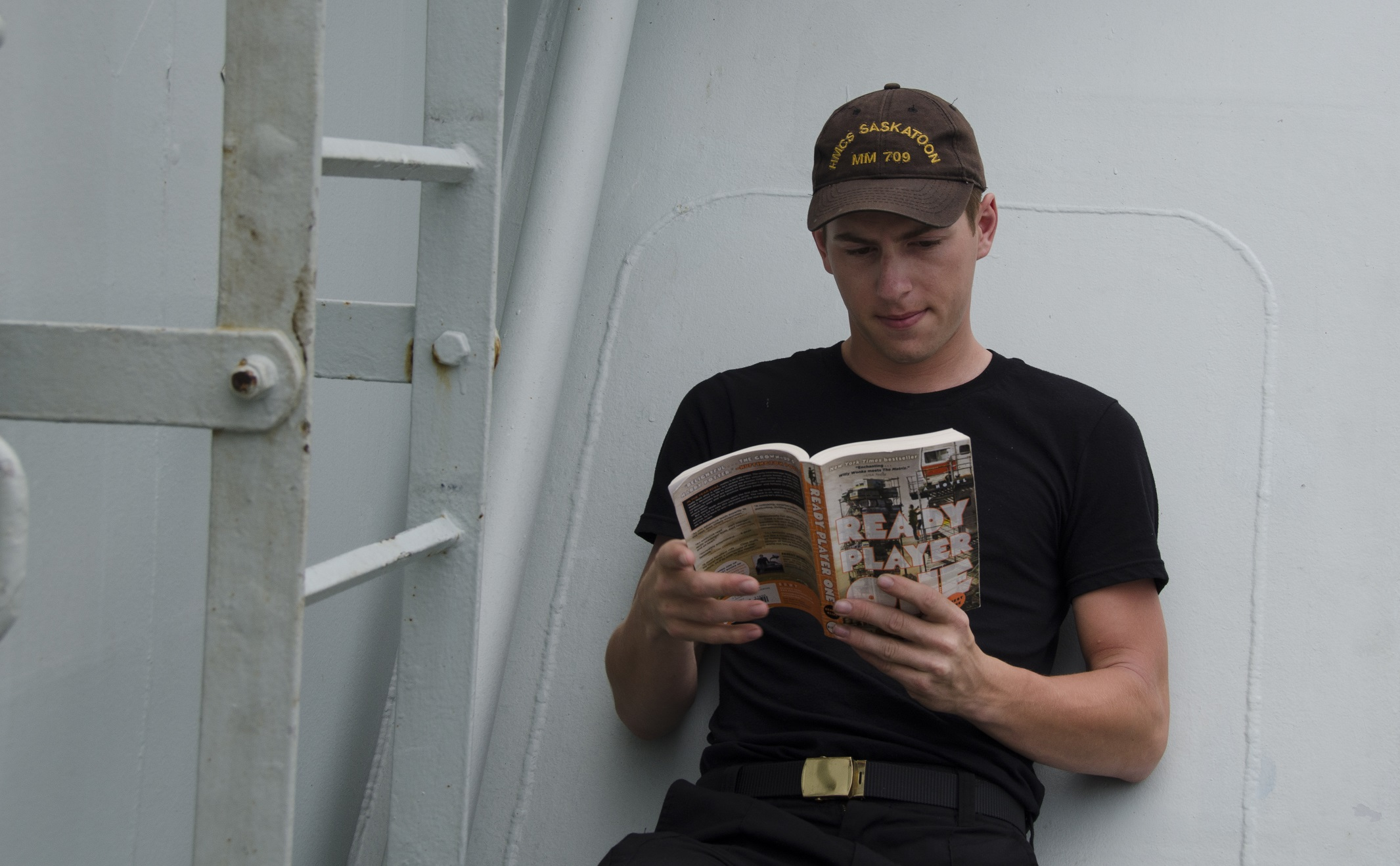 A sailor leans against a wall reading a book.