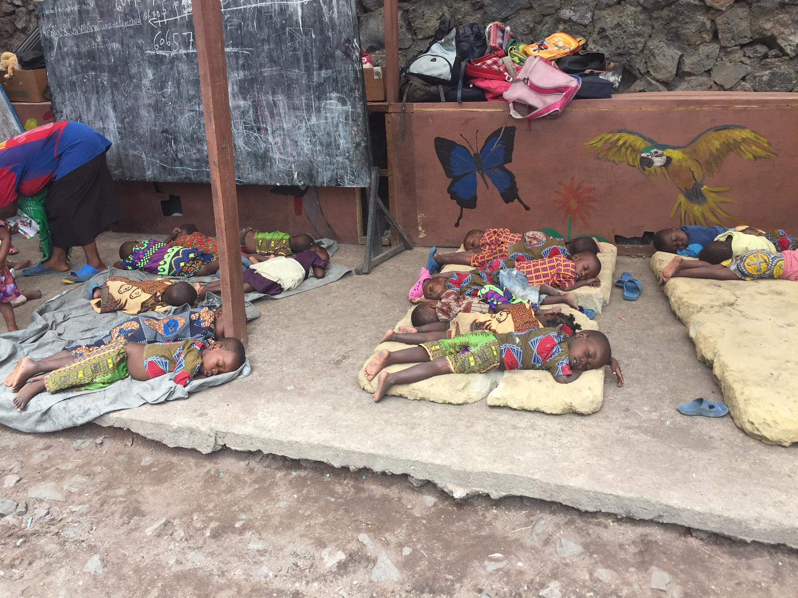 Children sleeping on blankets and mattresses.