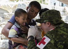 Sindhupalchok District in Nepal. 10 May 2015 – Captain Jonathan Bishop, doctor for the Canadian Armed Forces Disaster Assistance Response Team, treats a child in the village of Balephi, Sindhupalchok District in Nepal, during Operation RENAISSANCE 15-1. (Photo: MCpl Cynthia Wilkinson, Canadian Forces Joint Imagery Center)
