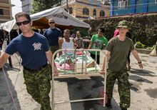 Japarti, Nepal. 14 May 2015 – Medical Assistant, Sergeant Kelly Finimore, firefighters, Corporal John Paul Clost, and Corporal Craig Fonger, transport a patient to a new location at the Nepal Orthopaedic Hospital. (Photo: MCpl Cynthia Wilkinson, Canadian Forces Joint Imagery Center )