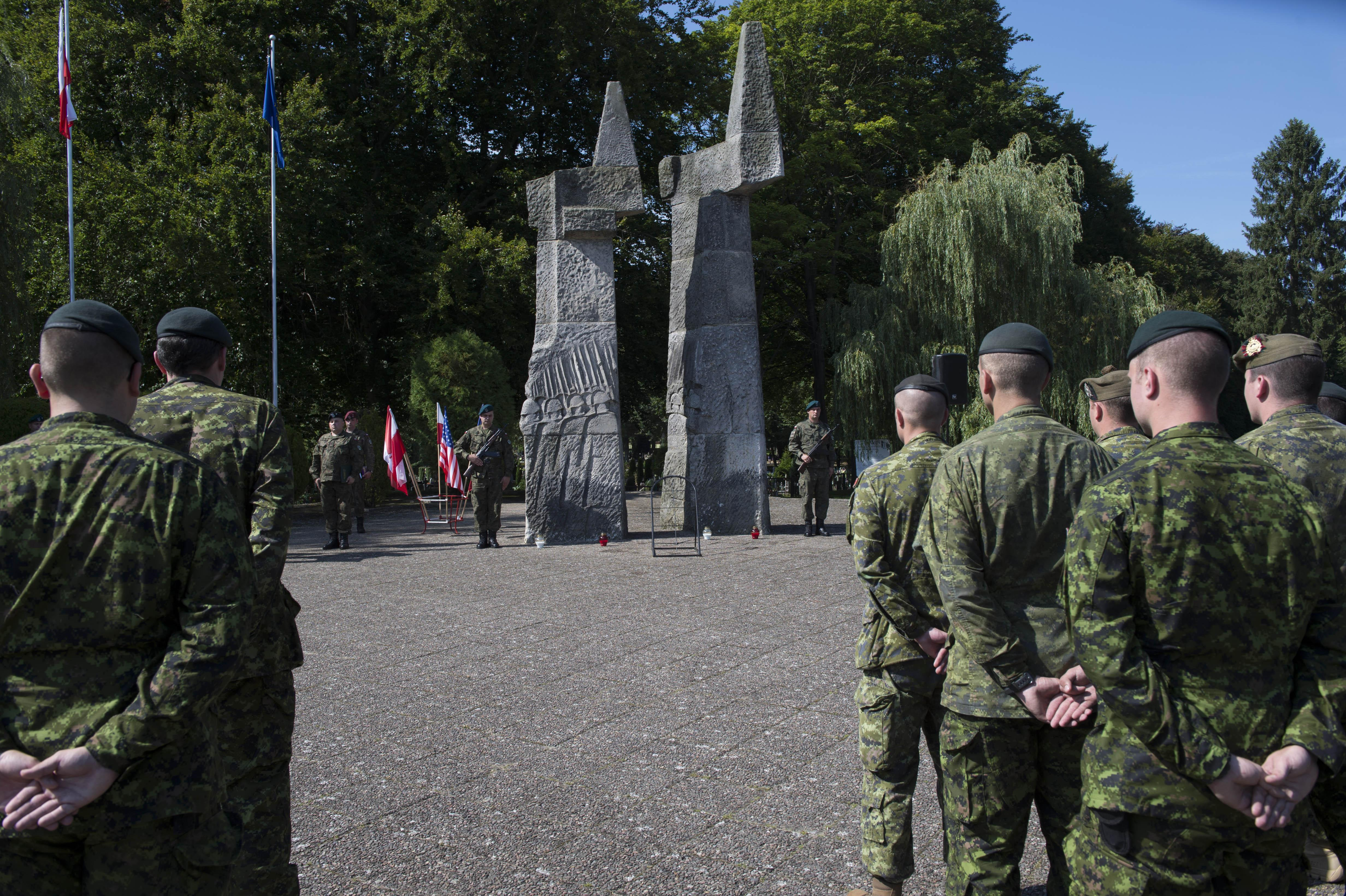 Soldiers face a monument.