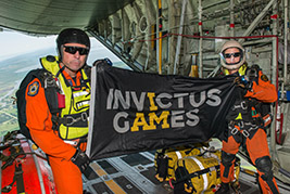 435 Squadron Search and Rescue technicians from Winnipeg, Man., held the Invictus Games flag on the ramp of the CC-130 Hercules aircraft just prior to a static line jump.