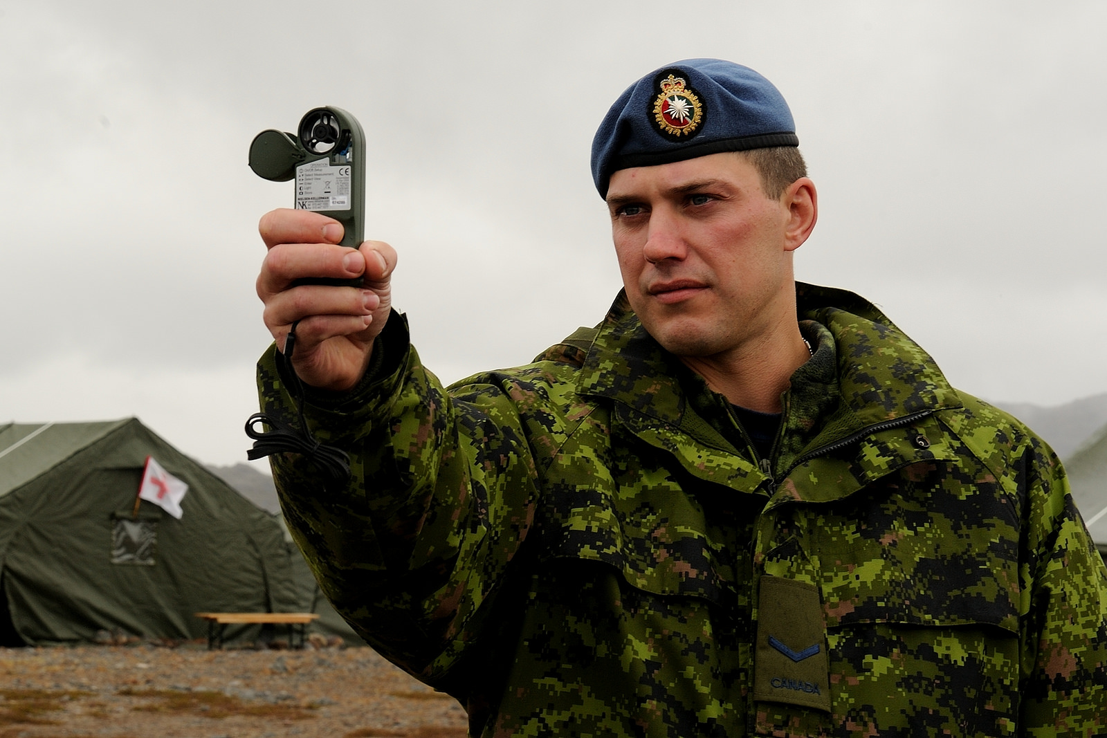 A soldier holds instrument up