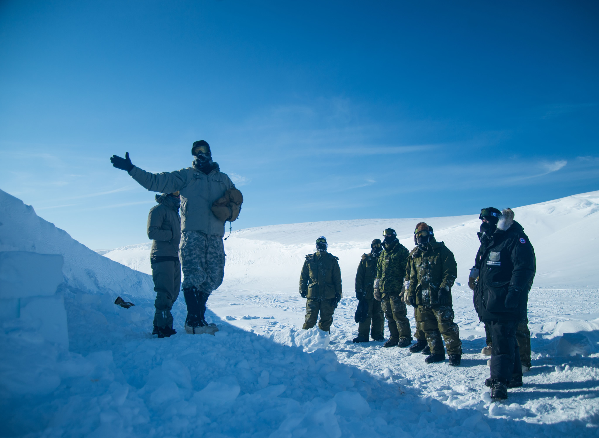 American Staff Sergeant Matt Hinds of the Northern Warfare Training Center instructs members of the 2nd Battalion, The Royal Canadian Regiment on the construction of a snow cave near Resolute Bay, NU, in preparation for Operation NUNALIVUT April 4, 2016. (Photo: Cpl Parks, Task Force Image Technician)