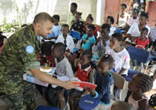 Port-au-Prince, Haiti. 18 October 2009 – Lieutenant Commander Shekhar Gothi, Operations and Plans Officer for United Nations MINUSTAH, hands out books to the children of the Compassion Orphanage located on the outskirts of Port-au-Prince, Haiti. (Photo: Corporal Shilo Adamson, Canadian Forces Combat Camera)