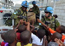 Port-au-Prince, Haiti. 16 September 2013 – Corporal Marc-Daniel Benoit (left) and Sergeant David Lapalme (right) from 2nd Battalion, Royal 22e Regiment give clothes and accessories to local children during Operation HAMLET. (Photo: MCpl Marc-Andre Gaudreault, Canadian Forces Combat Camera)