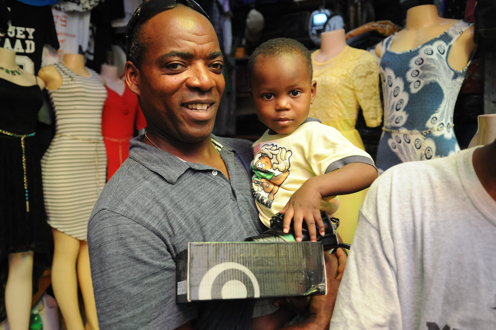 A man holds a toddler. Both pose for the camera.