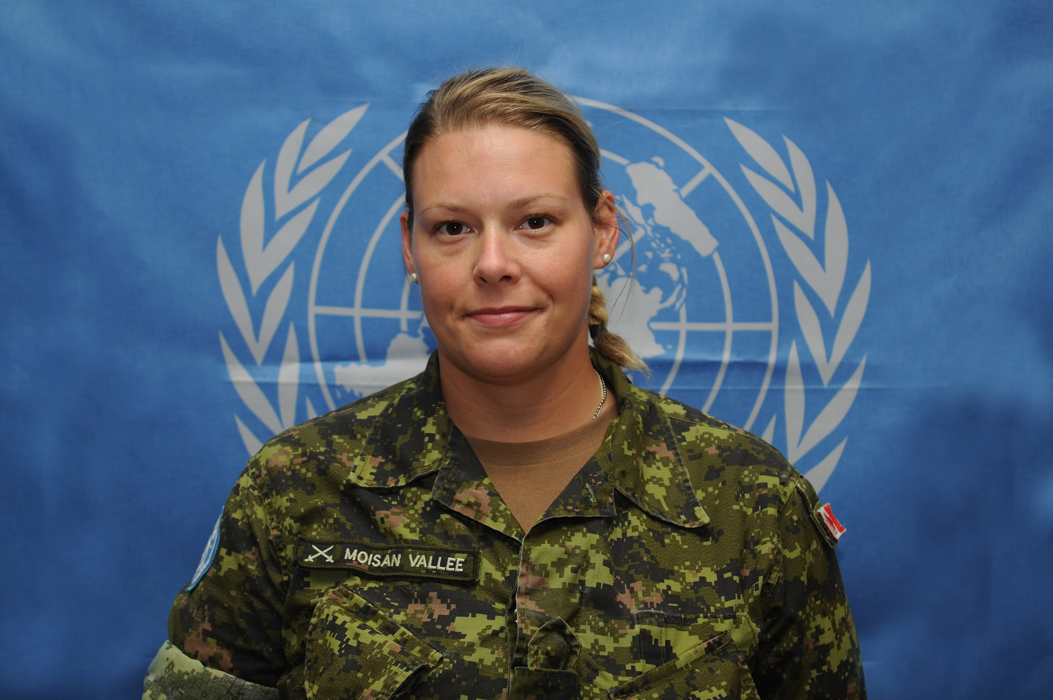 A female soldier stands in front of a blue background