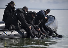 Estonia. 18 May 2015 – Royal Canadian Navy Clearance Divers assist other divers into to the water during a Silent Entry procedure used when diving near suspected underwater mines during OPERATION OPEN SPIRIT on May 18, 2015. The operation is a multi-national underwater mine clearing exercise being held near Estonia to rid the waters of mines that were laid during World War I and World War II. (Photo by: Cpl Chris Ringius, Formation Imaging Services Halifax)