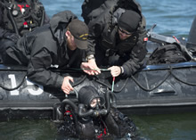 Estonia. 19 May 2015 – Royal Canadian Navy Clearance Divers assist a diver as they prepare to get out of the water during Operation OPEN SPIRIT on May 19, 2015. The operation is a multi-national underwater mine clearing exercise to rid the waters near Estonia of mines laid during World War I and World War II. (Photo by: Cpl Chris Ringius, Formation Imaging Services Halifax)