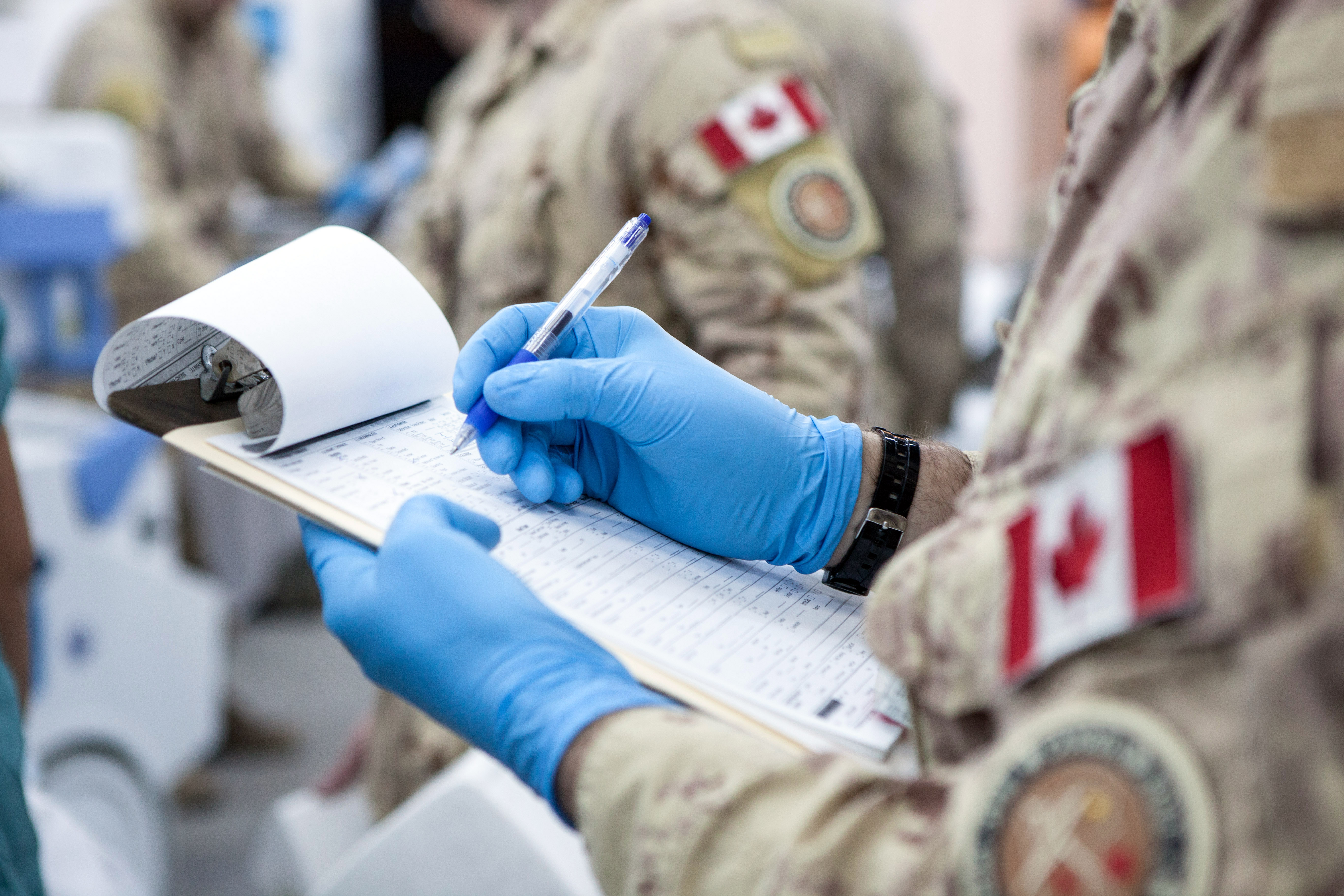 Military medical personnel takes notes.