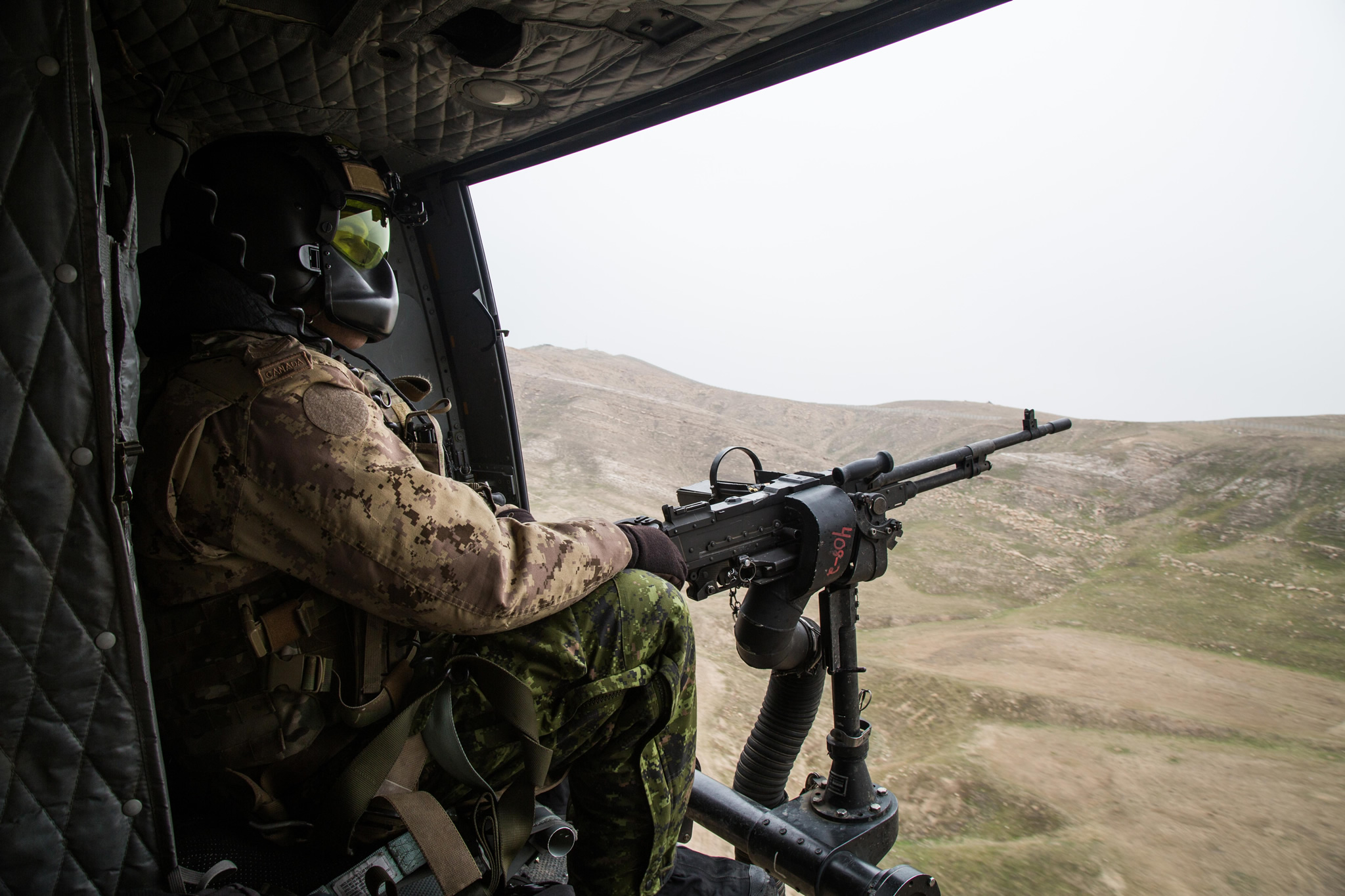 a military member looks out the side of a helicopter with a machine gun