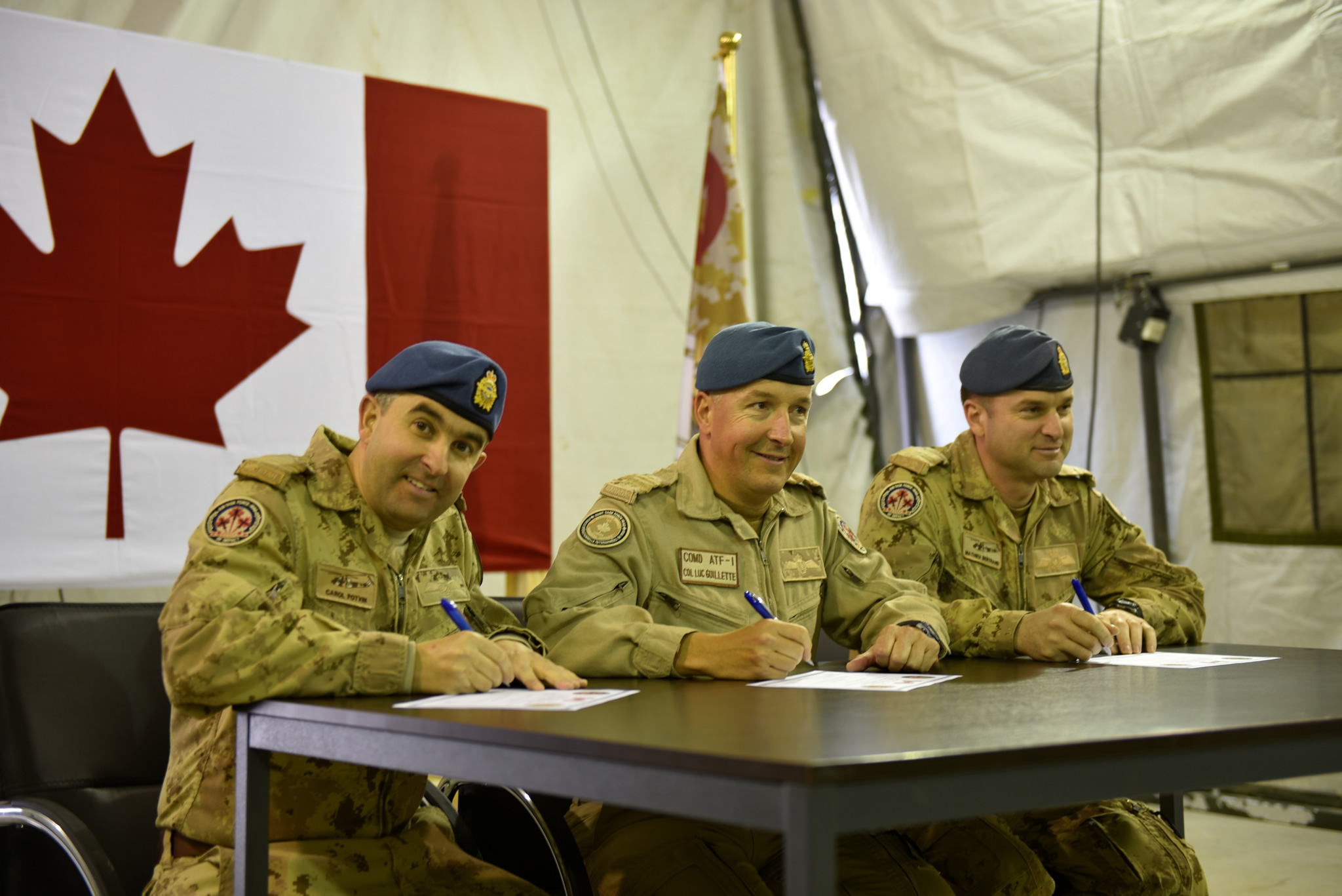 Three men in tan uniforms sit at a table in front of a Canadian flag and sign papers