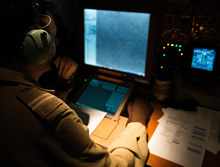 25 February 2015 - A Tactical Navigator onboard a CP-140 Aurora keeps a sharp eye on his monitor as part of a combat mission over Iraq during Operation IMPACT. (Photo: OP Impact, DND)
