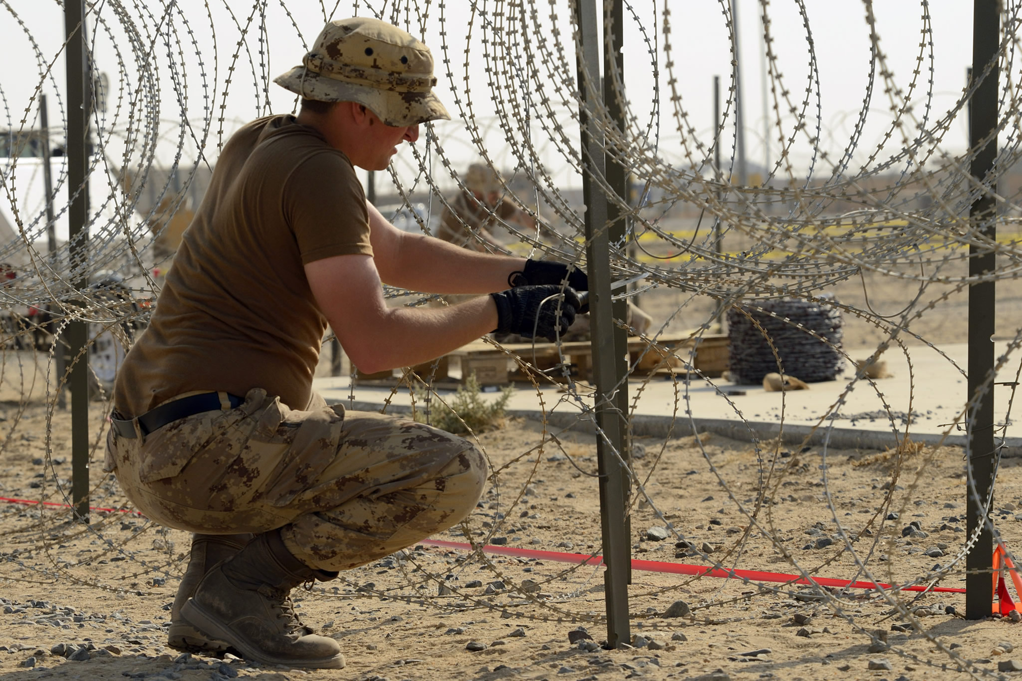 Kuwait. 14 November 2014 – A member of the Canadian Armed Forces reinforces concertina wire around the Canadian camp during Operation IMPACT on November 14, 2014 in Kuwait. (Photo GX2014-0052-170: Operation IMPACT, DND)