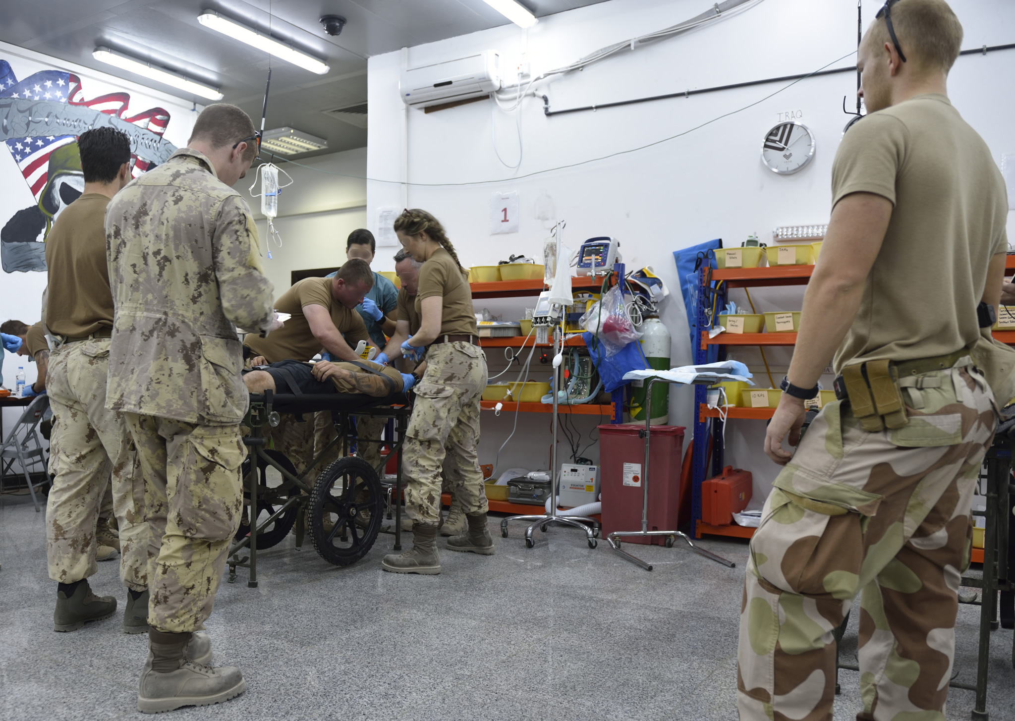 military medical staff surrounda patient on a bed with medical equipment in the background.