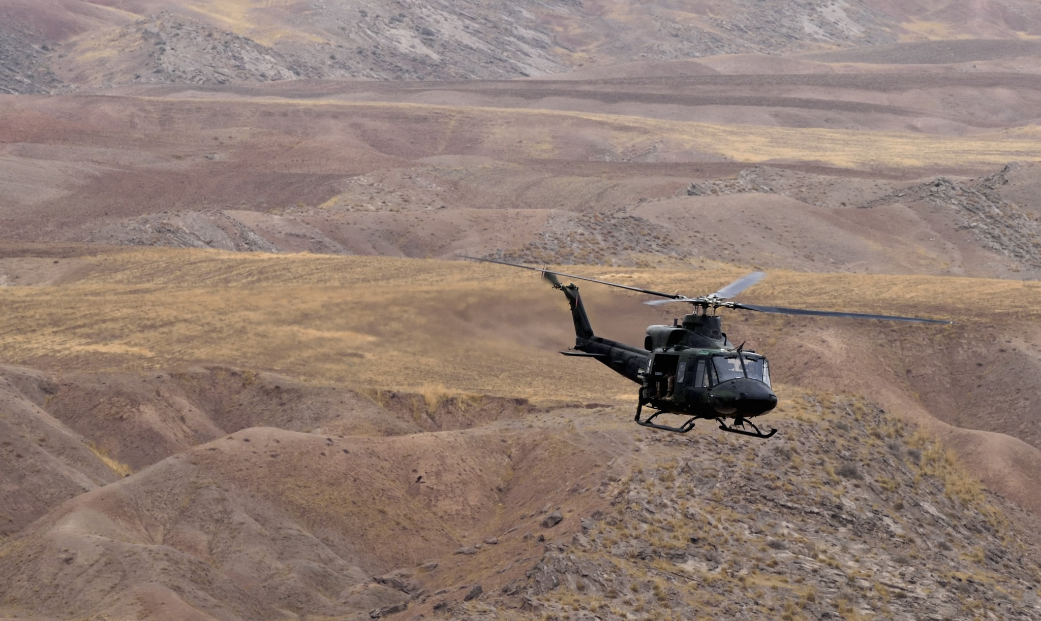 Helicopter flies over hilly landscape.