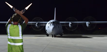 The Mediterranean. 6 September 2014 - A technician signals a CC-130J Hercules aircraft to stop on an airfield during Operation IMPACT in the Mediterranean on September 6, 2014. (Photo: MCpl Patrick Blanchard, Canadian Forces Combat Camera)