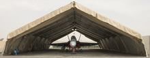 Camp Patrice Vincent, Kuwait. 26 May 2015 – A CF-188 Hornet jet sits inside a finished Modular Shelter System – Aircraft, at the Camp Patrice Vincent flight line in Kuwait during Operation IMPACT. (Photo: OP Impact, DND)