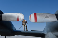 To keep the aircraft functioning properly in a desert environment, an aviation technician sprays down the wing and fuselage of a CP-140 Aurora in Kuwait during Operation IMPACT on April 4, 2016.