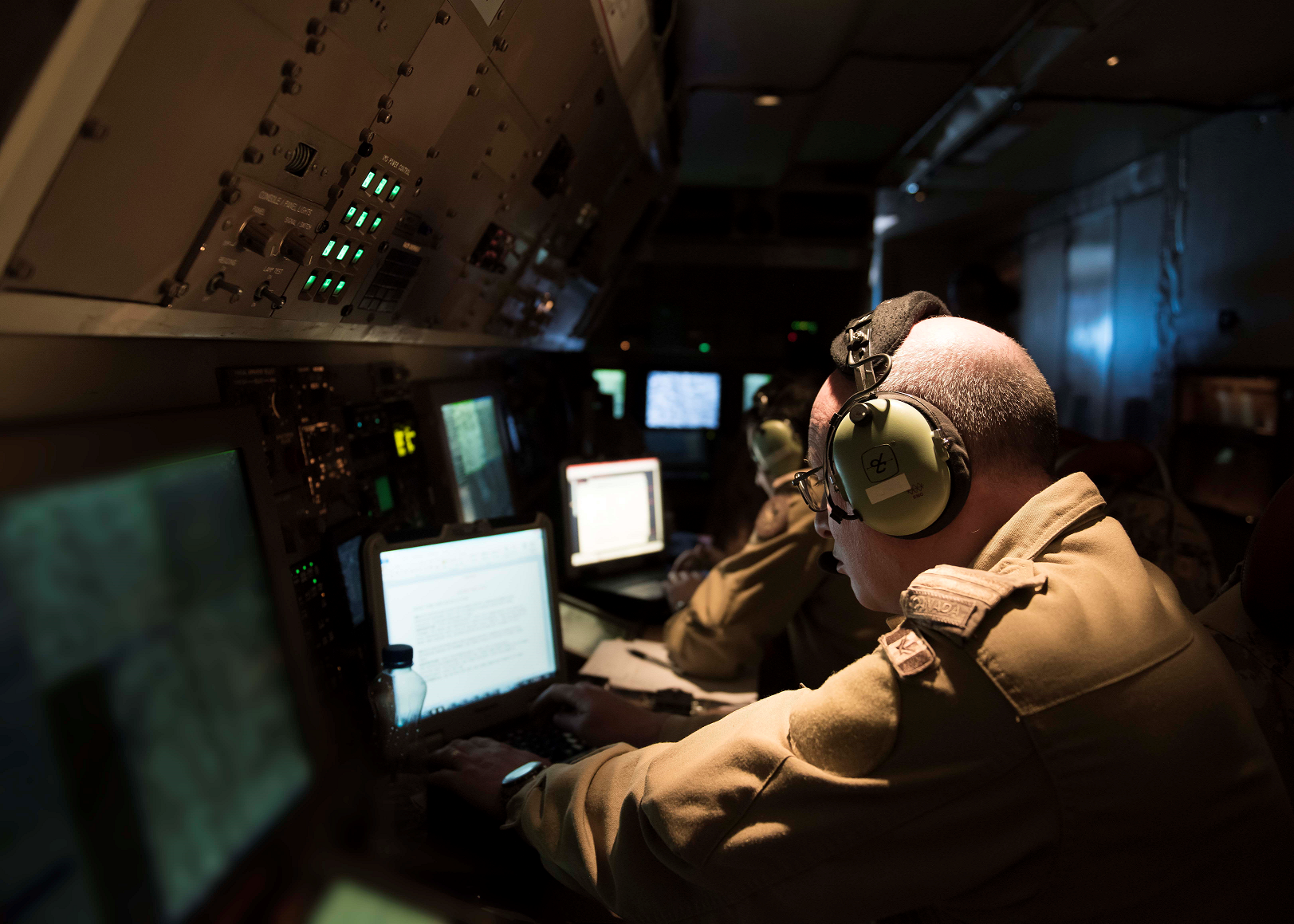 Air Combat System Officers onboard a CP-140 Aurora patrol aircraft log in their observations during a reconnaissance mission as part of Operation IMPACT on January 1, 2017. (Photo: Op Impact, DND)