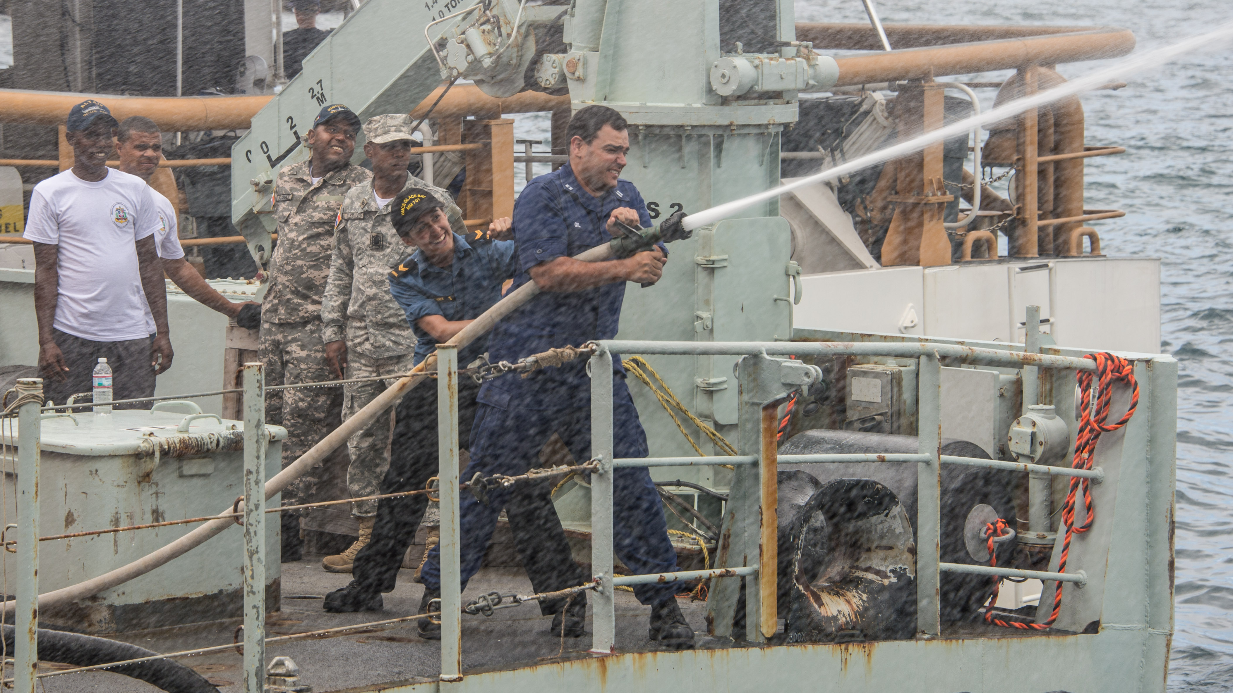 LS Vanessa Conde Torres, Marine Engineering Systems Operator on HMCS Glace Bay, stabilizes a member of the US Coast Guard as he operates the fire hose at maximum power during Ex TRADEWINDS in St. Kitts and Nevis, June 2015.