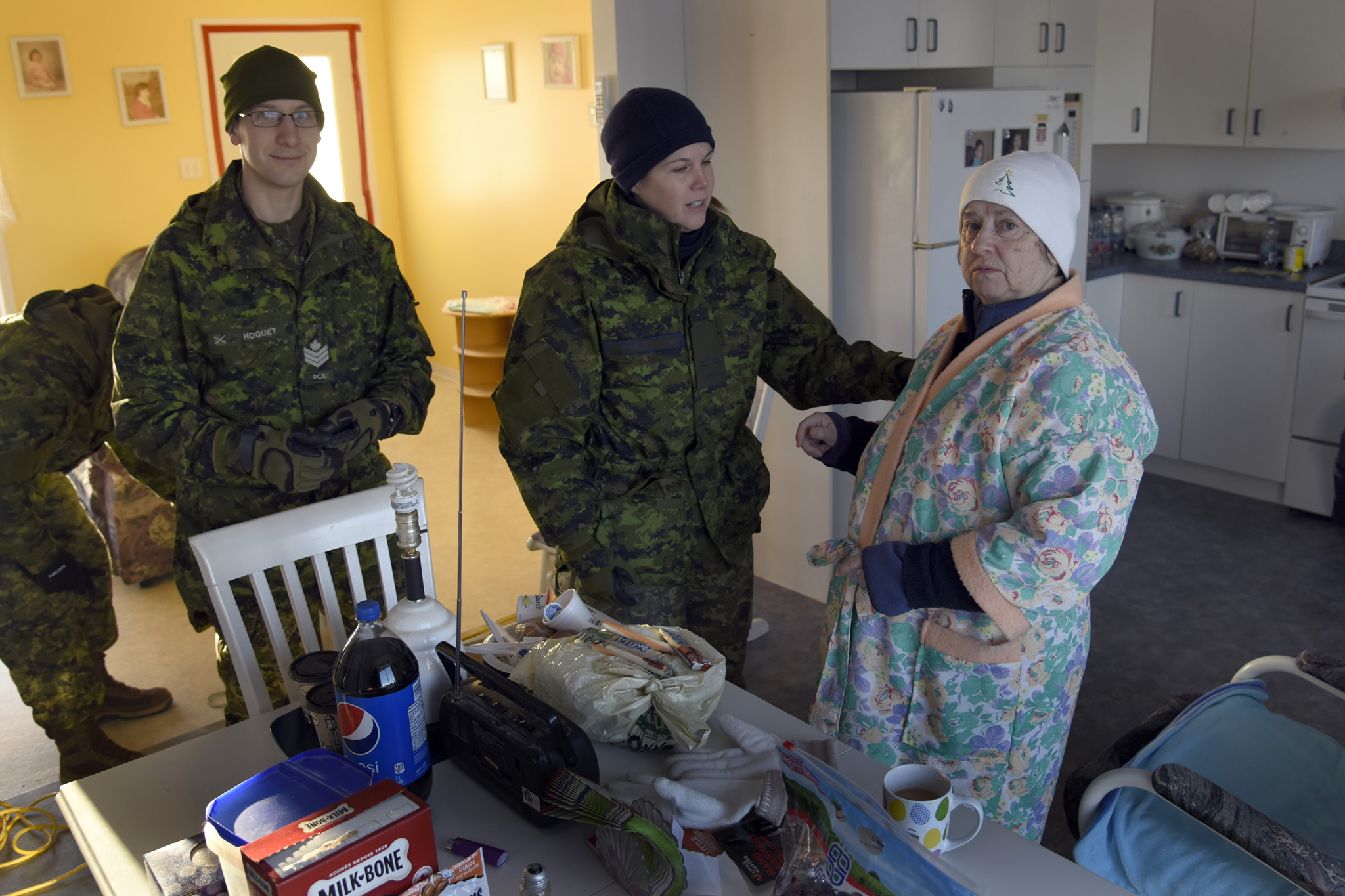 Sainte-Marie-Sainte-Raphael, New Brunswick. February 1, 2017 – Sergeant Benjamin Hoquet, 4th Artillery Regiment (General Support), and Aviator Suzanne Roussel, a Medical Technician with 42 Health Services, speak with a local resident to see if she has any concerns or needs after been without electricity for 8 days. Going door to door to check on residents was one of their many tasks during Operation LENTUS. (Photo by WO Jerry Kean/5 Cdn Div Public Affairs)