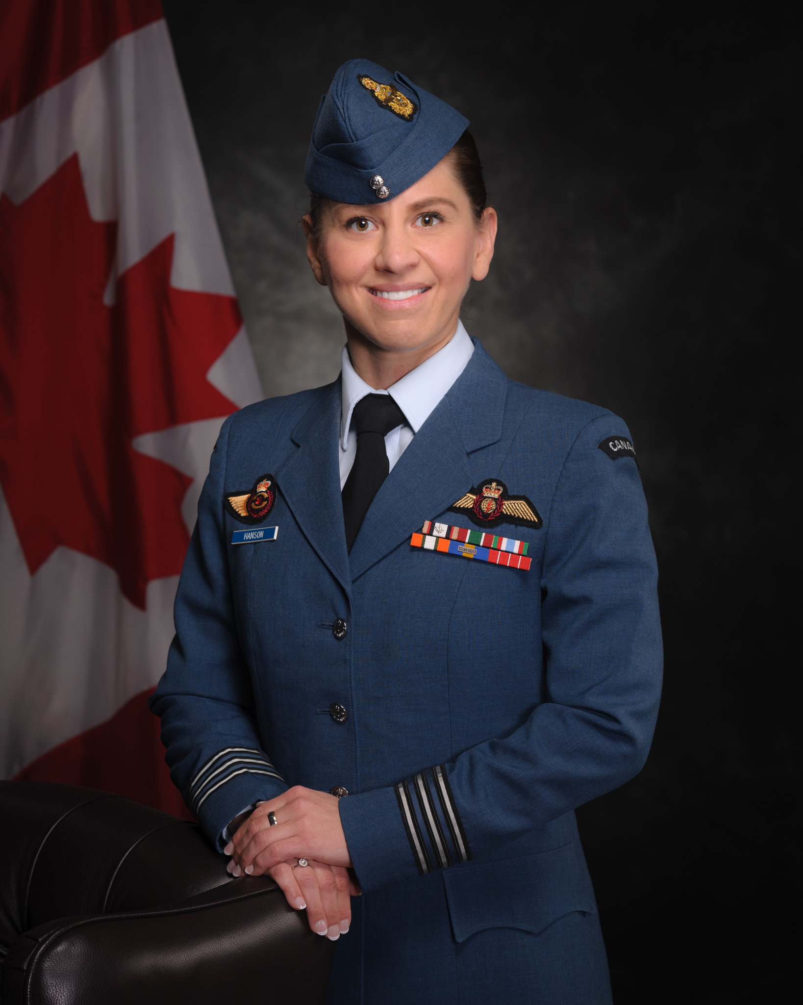 A woman in a blue military uniform smiles and stands in a formal pose