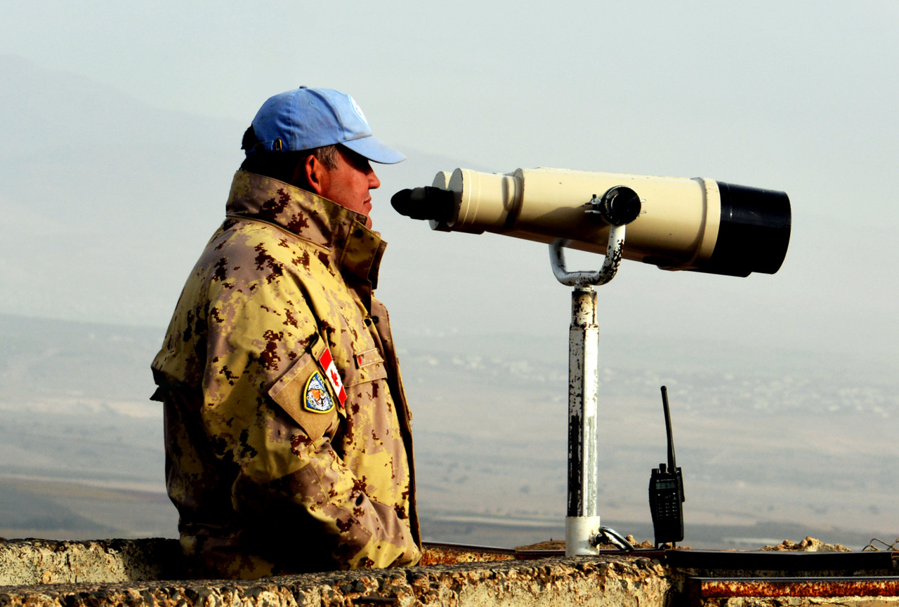 A soldier in a tan uniform stands beside very large binoculars