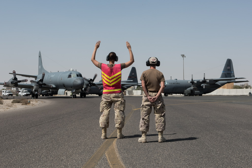 Two soldiers stand on a runway to help direct an aircraft.