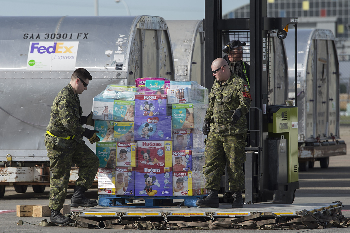 Traffic Technicians, Corporal (Cpl) Karl Webber (left) and Cpl Claude Lamarche, organize pallets of relief goods to be transported from Edmonton to Fort McMurray, Alberta, on May 7, 2016, as part of the Canadian Armed Forces' support to the Province of Alberta's emergency response to wildfires in Fort McMurray. Photo: Cpl Manuela Berger, 4 Wing Imaging
