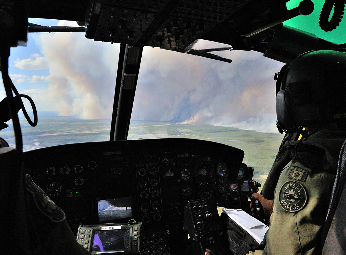 Members from 408 Tactical Helicopter Squadron, Edmonton fly a CH-146 Griffon to view the damage created by wild fires in the Fort McMurray area on May 5, 2016.The Canadian Armed Forces have air assets deployed in support of the Province of Alberta's wildfire emergency response efforts. Photo by: MCPL VanPutten, 3 CSDB Imaging