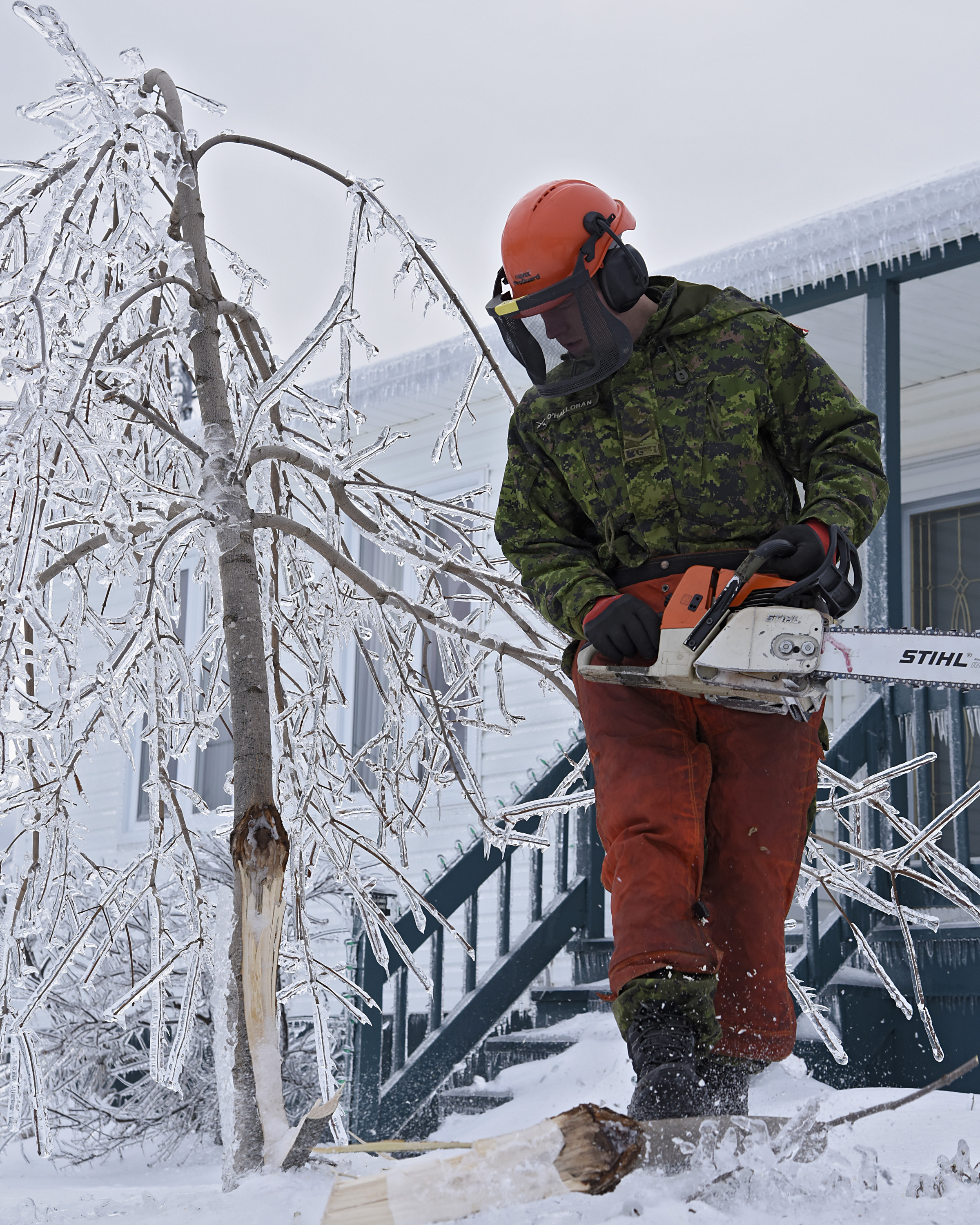 A soldier removes fallen tree branches from a frozen tree.