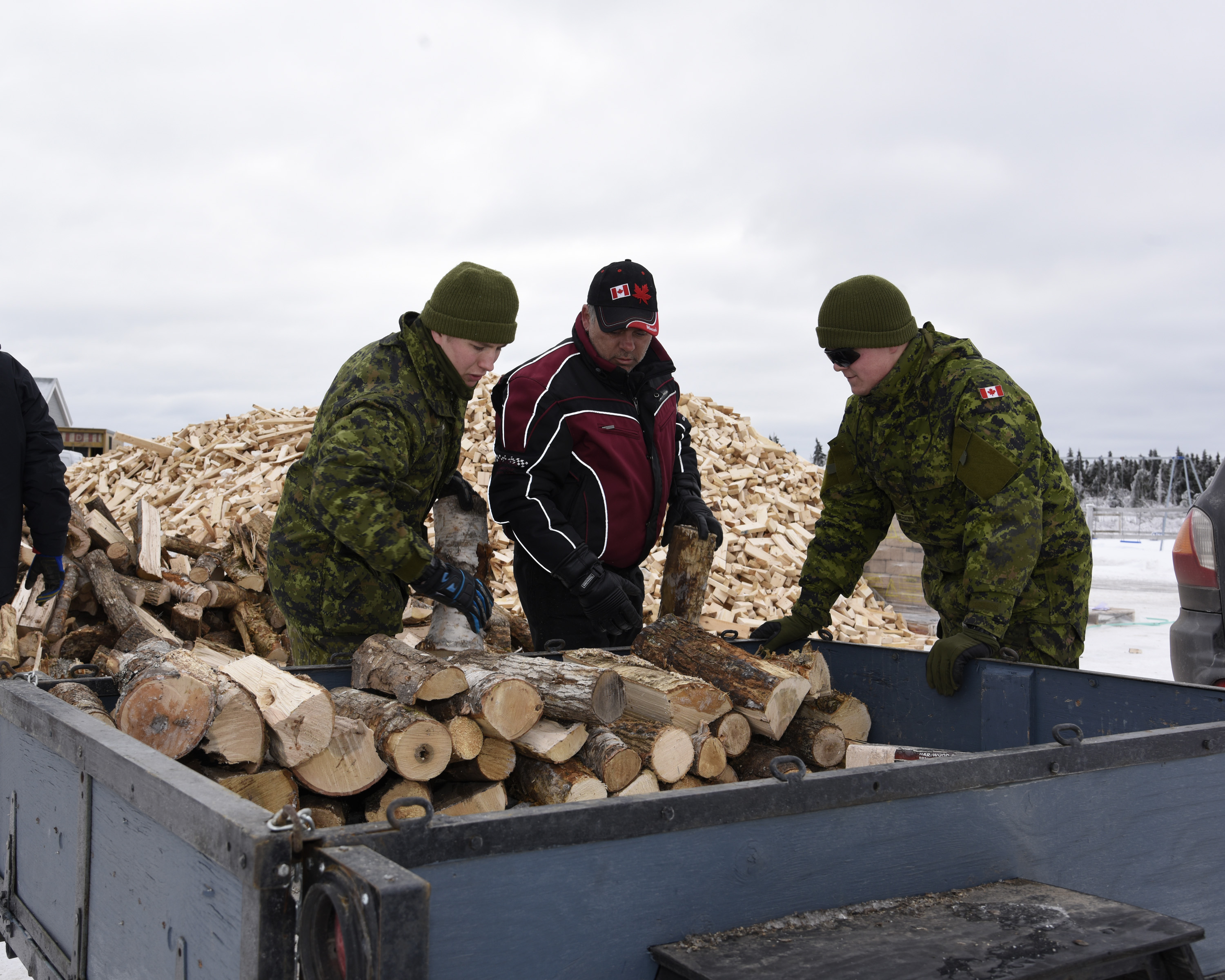 January 31, 2017. Gunner Dillon Ellis and Sapper Sergey Novikov, members of 4th Artillery Regiment (General Support) disperse fire wood to local residents in Sainte-Marie-Sainte Raphael New Brunswick during Operation LENTUS in the Acadian Peninsula of New Brunswick on January 31, 2017. (Photo: WO Jerry Kean, 5 Cdn Div Public Affairs)