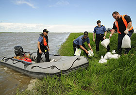 Members of Her Majesty Canadian Ship CHIPPAWA and local civilians load up sandbags for an aqua dam at Portage Diversion to help reduce damage from flooding during Operation LENTUS on July 7, 2014. Photo: Corporal Darcy Lefebvre, Canadian Forces Combat Camera