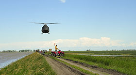 Portage la Prairie, Manitoba. 7 July 2014 - A CH-146 Griffon helicopter investigates the flood damage by the Portage Diversion near Portage la Prairie, Manitoba during Operation LENTUS 14-05. (Photo: Corporal Darcy Lefebvre, Canadian Forces Combat Camera)