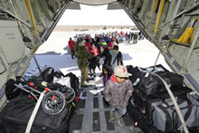 Kashechewan, Ontario. 12 May 2014 – A CAF member helps to load passengers from the First Nations community of Kashechewan on a CC-130 Hercules aircraft to provide air evacuation assistance from localized flooding. Over eight flights were completed by the CAF during Operation LENTUS 14-01 to evacuate approximately 1,500 people from Kashechewan. (photo by Sgt Daren Kraus).