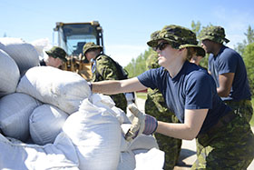 Lieutenant Marla Haring from 402 Squadron helps move sandbags in preparation for flooding across the Manitoba region in support of Operation LENTUS just outside St. Francois Xavier, July 7, 2014. Photo: Cpl Paul Shapka, 17 Wing Imaging