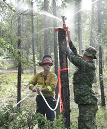 Whitehorse, Yukon. 7 August 2013 - A member of the Immediate Reaction Unit and a member of the Wildland Fire Management of Yukon, inspect a sprinkler system used in forest fire control operations during Operation NANOOK 2013. (Photo: MCpl Patrick Blanchard, Canadian Forces Combat Camera)