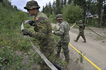 Whitehorse, Yukon. 8 August 2013 - Cavalier Guillaume Tremblay-Duchesneau, Corporal Eric Aubin and Corporal Yannick Roch of the Immediate Reaction Unit from the Royal 22e Régiment from Valcartier, Québec carry a sprinkler hose designed to help suppress a simulated wild-fire near the suburb of Riverdale during Operation NANOOK 2013. (photo by Sergeant Vaughan Lightowler, Canadian Forces Combat Camera)