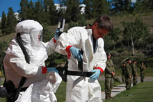 Whitehorse, Yukon. 6 August 2013 - Members of Health and Social Services of the Government of Yukon, assisted by the Immediate Reaction Unit from Royal 22e Régiment, Valcartier, Québec, conduct a biohazard contol training scenario during Operation NANOOK 2013. (Photo: SLt Eliane Trahan, Canadian Forces Combat Camera Public Affairs Officer)