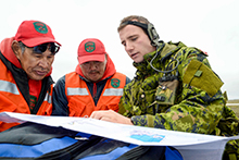 Captain Matthew Szostk (right), from The Royal Montreal Regiment discusses route options with members of 1 Canadian Rangers Patrol Group, Master Corporal Andy Aliyak (left), and Ranger John Ussak (center) near Rankin Inlet, Nunavut during Operation NANOOK, August 21, 2016. (Photo: Petty Officer Second Class Belinda Groves, Task Force Imagery Technician)