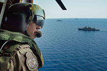 September 15 2016. A member of Her Majesty's Canadian Ship (HMCS) CHARLOTTETOWN's Air Crew waves looks on as Greek Navy Frigate Spetsai (F453) (bottom), HMCS CHARLOTTETOWN (top) and Italian Navy Frigate Virginio Fasan (F591) (middle) during Operation REASSURANCE in the Mediterranean Sea, September 15 2016. (Photo: Cpl Blaine Sewell, Formation Imagery Services)