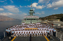 The crew of Her Majesty's Canadian Ship (HMCS) CHARLOTTETOWN gathers on the foc'sle of the ship for a group photo while alongside in Souda Bay, Crete, Greece during Operation REASSURANCE, August 9, 2016. (Photo: Cpl Blaine Sewell, Formation Imaging Services)